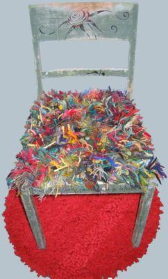 """""""Ryijytuoli ja -matto"""" Työn lähtökohtana oli satu, Anni Swanin ihmekukka. Tuolin nukkaan käytin koulun vanhoja lankakarttoja - pellavaa, villaa, paperinarua - eri vahvuuksia ja eri käyttötarkoituksiin tarkoitettuja lankoja. Langat pujotin (ei solmuja) jutikankaalle (säkkikangas) virkkuukoukulla. Mattoon käytin puuvillatrikoista matonkudetta. Nukan pujottelin virkkuukoukulla lenkeiksi liukuestemattoon, jossa on noin sentin suuruisia reikiä. Osan lenkeistä leikkasin auki ja osan jätin lenkeiksi. Maton pohjan tuin ryhdikkäällä sekoitekankaalla, jonka ompelin käsin kiinni verkkoon.  Ursula Finni, Savonlinnan OKL Kuva ja www-sivu Tarja Kröger"""